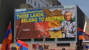 """Demonstrators carry a sign that reads """"These lands belong to Armenia"""" with a map of Turkey (Credit: Democracy Now!)."""