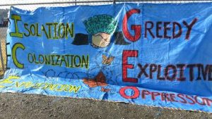 A banner outside the Northwest Detention Center in Tacoma reads: Isolation Colonization Exploitation (ICE) and Greedy Exploitative Oppression (GEO). (Credit: Democracy Now!)