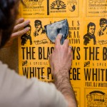A student from the program uses wheat paste to post flyers examining white privilege and the relationship between citizens and police. Photo by Andrew Jeffers