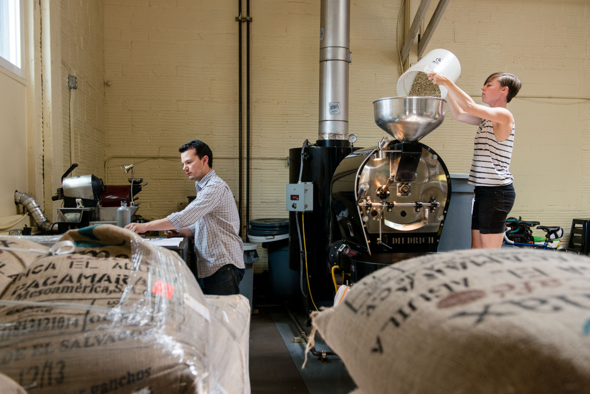 Oliver Stormshank and an employee use a Diedrich IR-12 to roast small batches of green coffee beans at Olympia Coffee Roasting Company. The local business was named 2013 Micro Roaster of the Year by Roast Magazine.