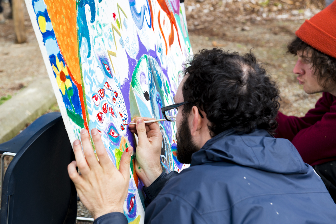 Evergreen student and artist Leo Shallat contributes his artistry to the community mural being created for the Serenity Garden, during the 2013 Harvest Festival at the Organic Farm. Sat., Oct. 12 2013