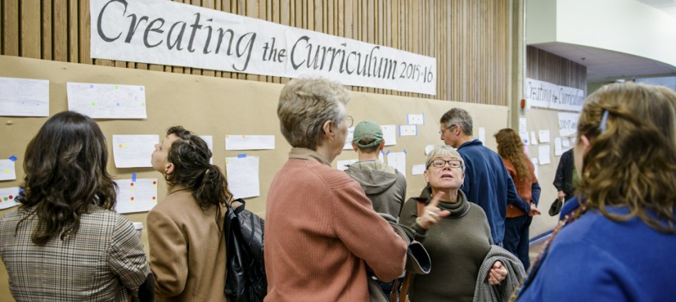 Faculty talking in front of the curriculum wall