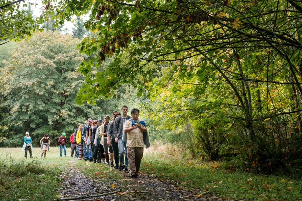 Jamyang Tsultrim of the Counseling Center leads a group of students through the forest . Sept. 24th